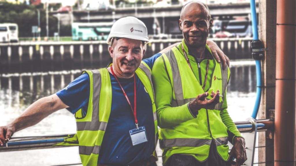 Two workers standing together in their workplace discussing compensation.